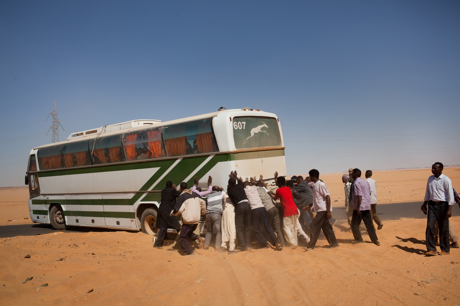 Migrants assist in moving a bus stuck in the sand on the road from Kufra, southern Libya, to Ajdabiya, in the north on March 7, 2012.