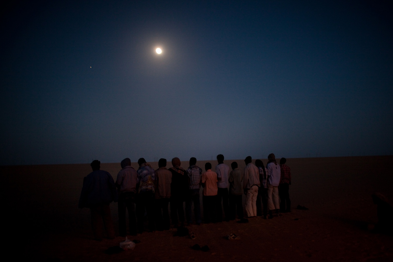 Muslim migrants gather for evening prayers off the side of the road en route to Ajdabiya, from Kufra, southern Libya on March 7, 2012.