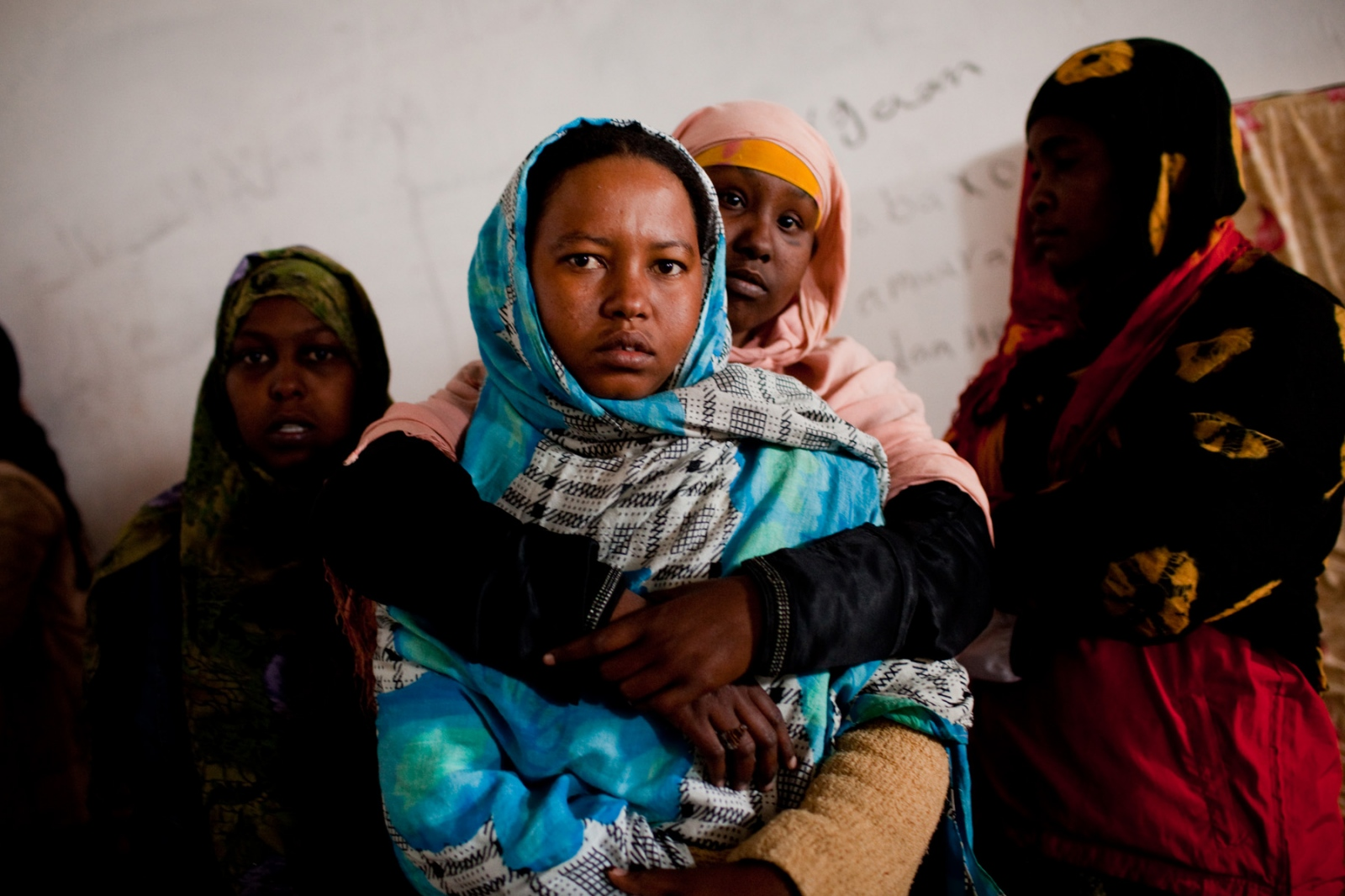 Somali and Eritrean women gather in a room at the Ganfuda detention facility in Benghazi on March 3, 2012. Some have been there for approximately two months after being held in Kufra, southern Libya. Most people paid at least $2000USD to get from their home countries to Kufra, crossing the Chad-Libya border illegally to seek work in Libya, or to advance their journey on to Europe.