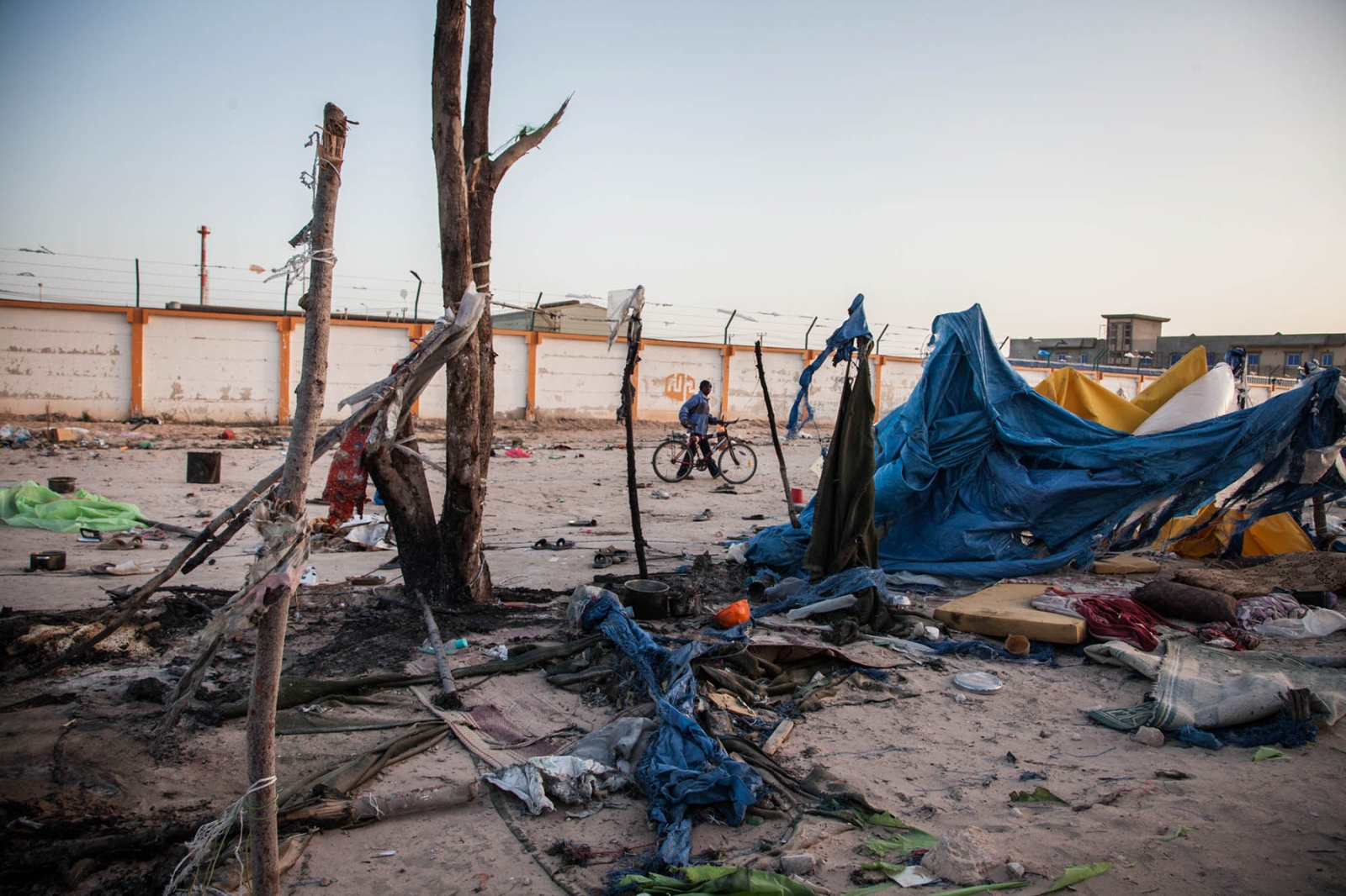 An African migrant worker gathers the few belongings he had and moves out of the destroyed section of a tent camp near the port of the besieged city of Misurata on April 26, 2011, after a shell from pro-Gaddafi forces landed in the camp, killing one migrant and wounding several others.