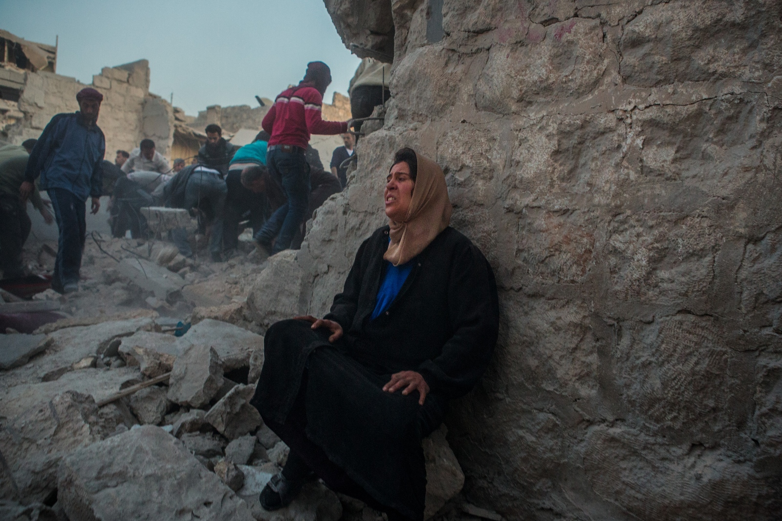 A woman cries in despair amidst the rubble of her neighborhood moments after an aerial bombardment released four to five parachute bombs in the Karm Homed neighborhood of Aleppo, Syria, on Monday, March 18, 2013. Approximately 26 people were killed and over 60 were injured.