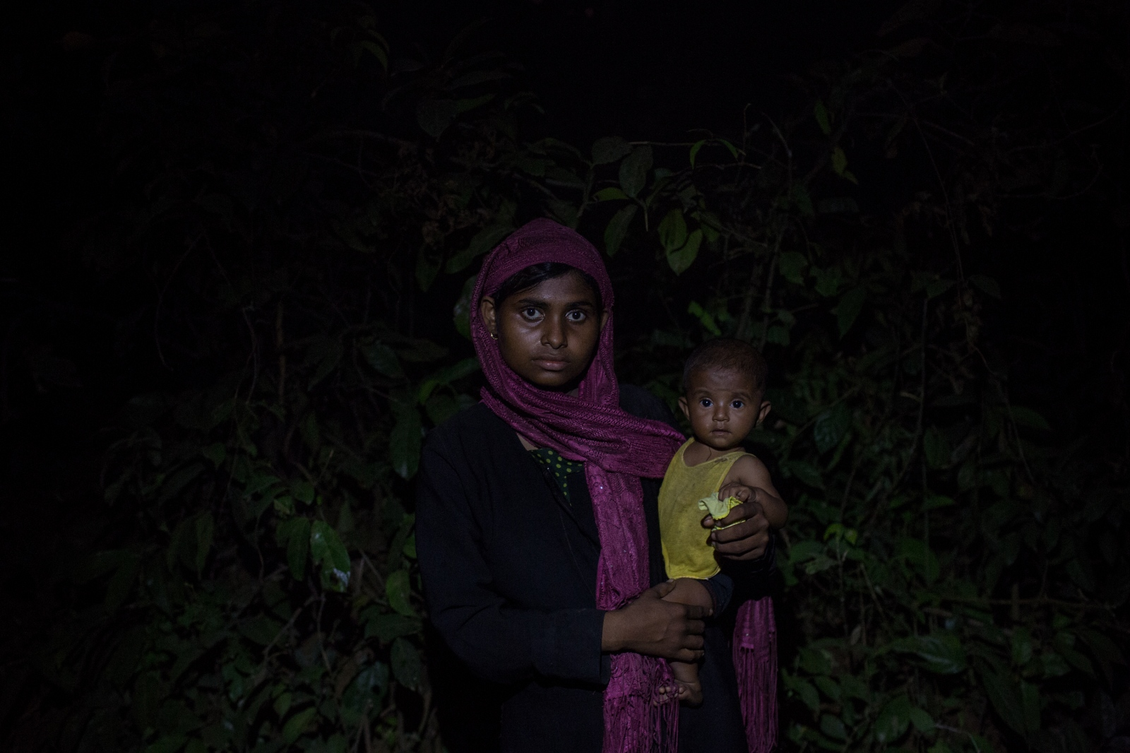 Settera, 25, waits on the side of the road for food and cash distributions with one of her two children near the Balukhali refugee camp in Bangladesh, on Friday, September 22, 2017. Settera's husband remains in Myanmar although she does not know of his fate since the military entered her village and forced people to flee.