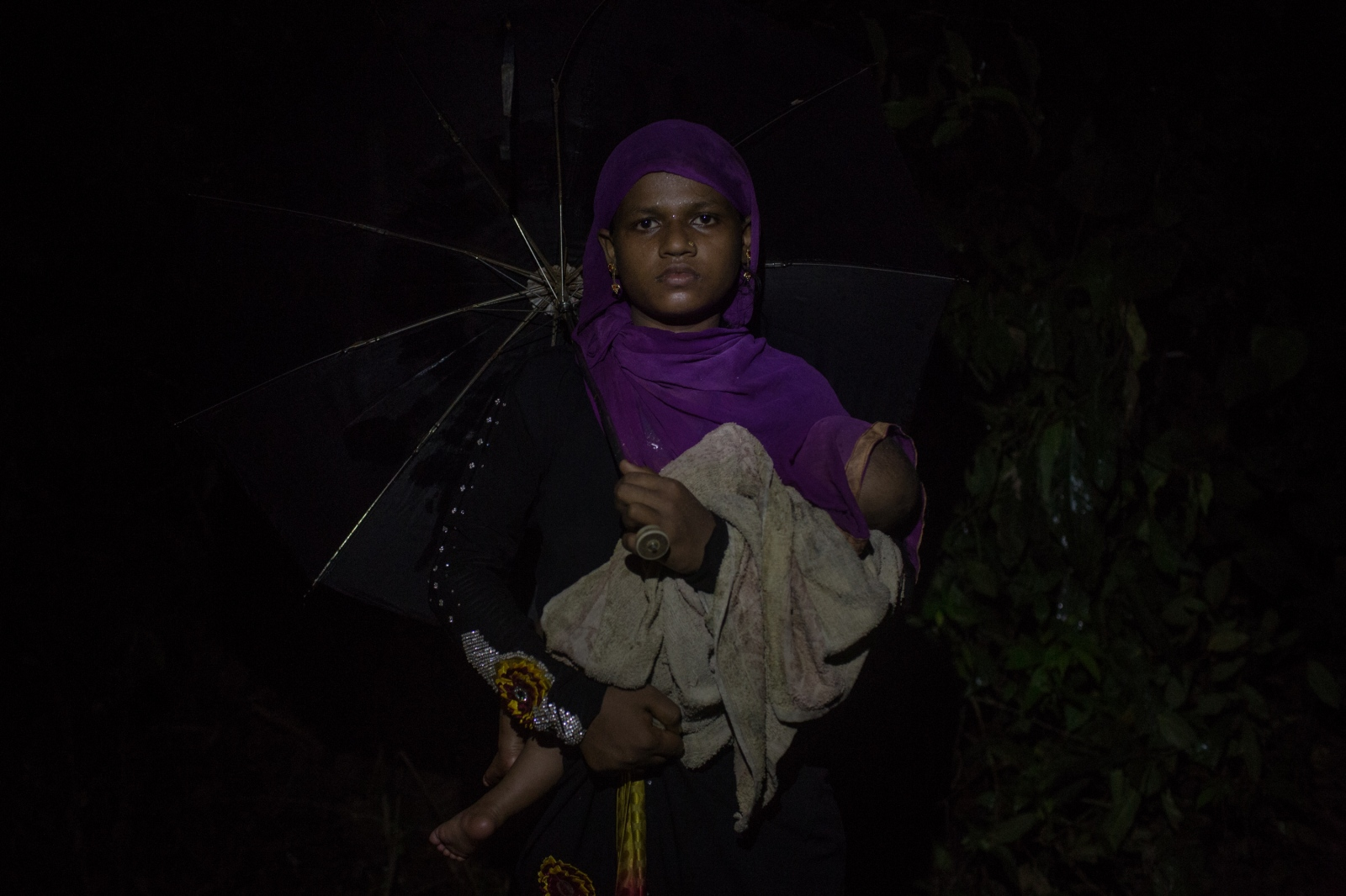 Samira, 20, waits with her baby by the side of the road for food and cash distributions near the Balukhali refugee camp in Bangladesh on Saturday September 23, 2017. Samira was separated from her husband after being attacked by the Burmese Army in the Buthidaung Township. She does not know what happened to him.