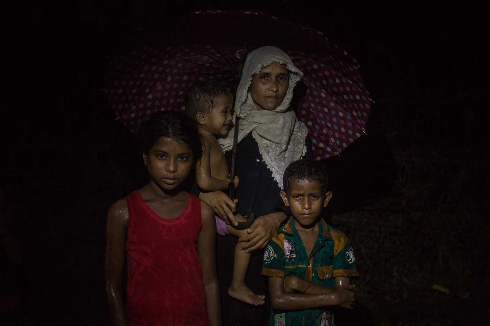 Fatima Khatoon, 30, waits with three of her four children by the side of the road for food and cash distributions near the Balukhali refugee camp in Bangladesh on Saturday September 23, 2017. Fatima arrived 21 days ago after fleeing from her village in the Buthidaung Township. She does not know where her husband is, or if he is alive. They became separated after they Burmese Army attacked their village.