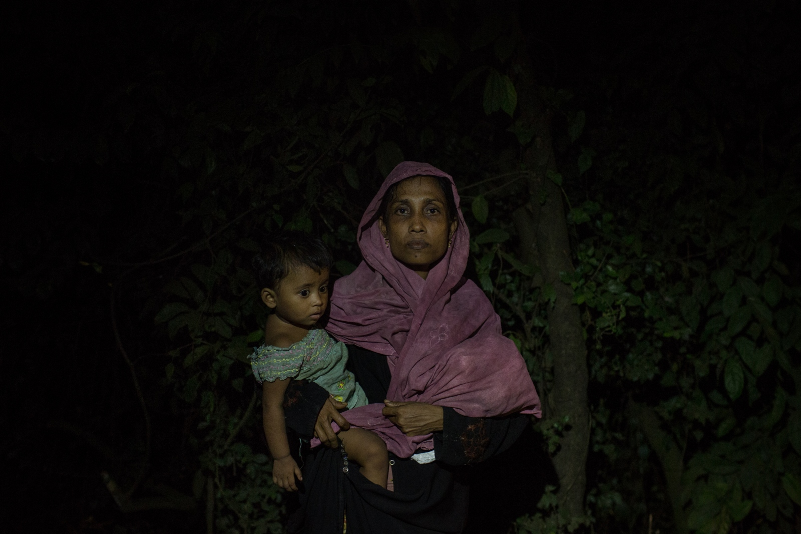 Anwara, 22, waits with one of her two children by the side of the road for food and cash distributions near the Balukhali refugee camp in Bangladesh on Friday September 22, 2017. Anwara's husband was a day laborer and was killed 18 days ago by the Buddhist militias in her village. She arrived in Balukhali 12 days ago.