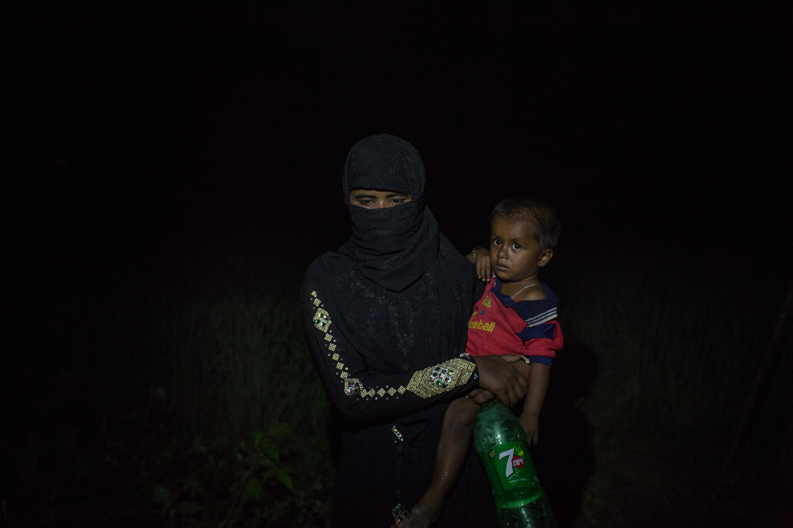 Rashida Begum, 22, waits with her son by the side of the road for food and cash distributions near the Balukhali refugee camp in Bangladesh on Friday September 22, 2017. Rashida's husband was asleep inside their home when the army arrived and set their house alight, with him still inside. He died in the fire, and Rashida was forced to flee.