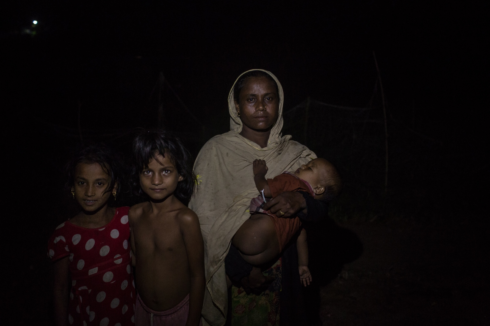 Romeeja Begum, 30, waits with her three children by the side of the road for food and cash distributions near the Balukhali refugee camp in Bangladesh on Friday September 22, 2017. Romeeja's husband remains in Myanmar but she does not know of his fate.