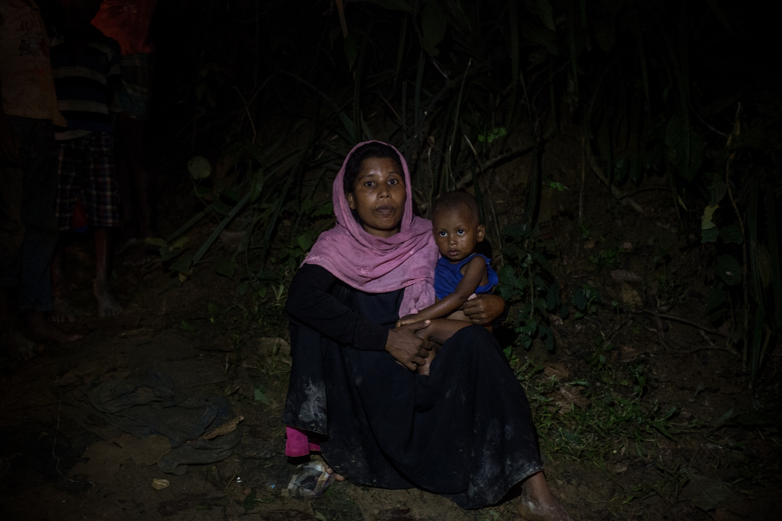 Fatima Fatoon, 25, waits by the side of the road for food and cash distribution with her son near the Balukhali refugee camp, Bangladesh on Friday, September 22, 2017. She has three children who she fled her village with when the Burmese military attacked and burned their homes. In the chaos, she became separated from her husband and he is still in Myanmar, although she does not know if he is alive.