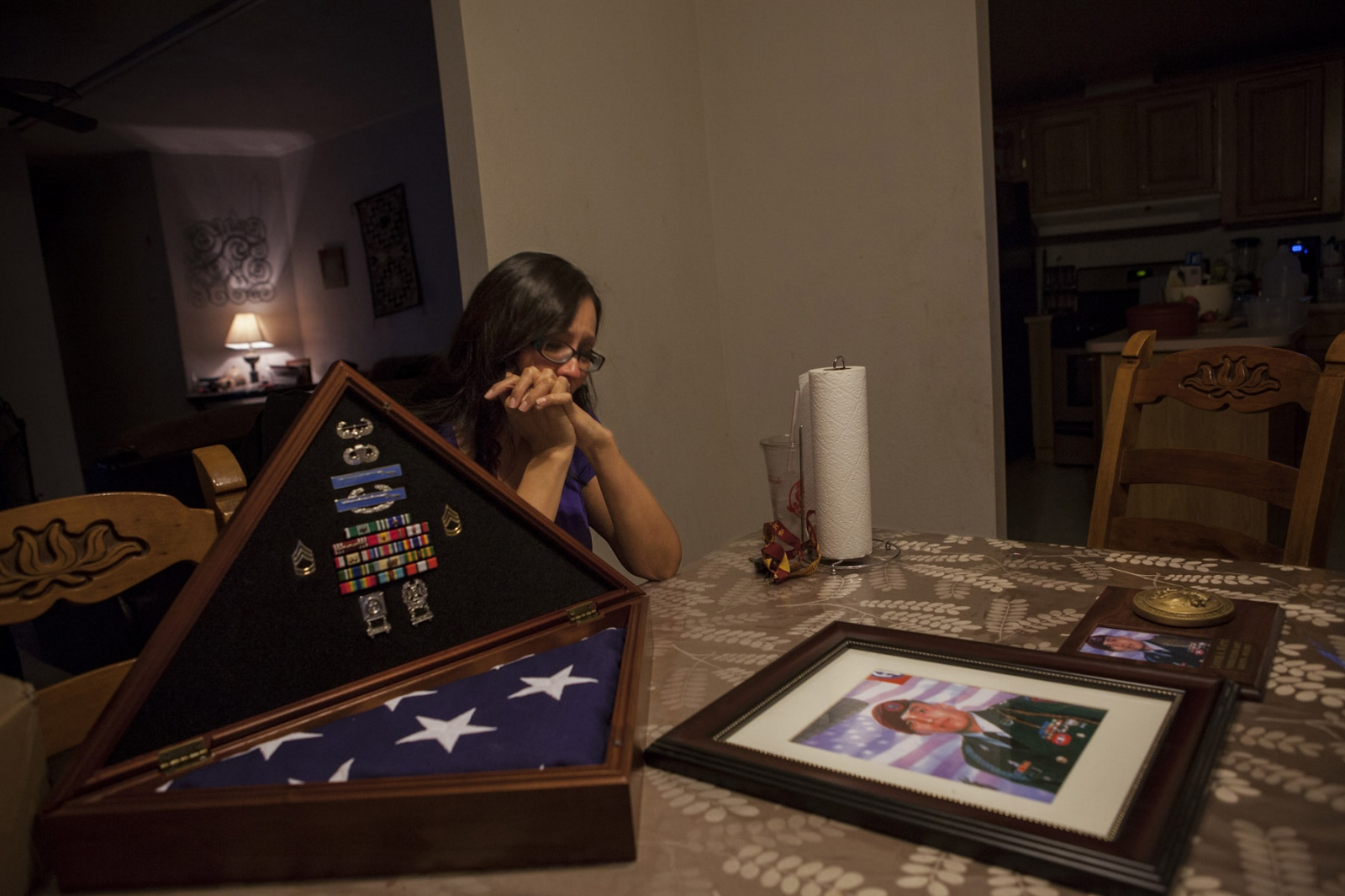 "Latonya ""Tasha"" Johnson, 35, sits at the dining table with the burial flag of her former husband Staff Sergeant Lonnie A. Watts, at their home in Rock Springs, New Mexico. 2014. Mr. Watts was deployed to Afghanistan after the start of the US-led invasion with the 82nd Airborne, an airborne infantry division and was later deployed to Iraq in 2005. Ms. Johnson believes that her husband, whom she met after he returned from Afghanistan, was deeply affected by what he'd experienced in combat there, but refused to seek help or counseling to get diagnosed with PTSD because it was something ""[he] was not proud of."" Mr. Watts turned to alcoholism to deal with the trauma and according to Ms. Johnson, always needed an adrenaline rush. Ms. Johnson says she wishes her husband could have sought counseling so that he would be alive today to help her raise their five children."