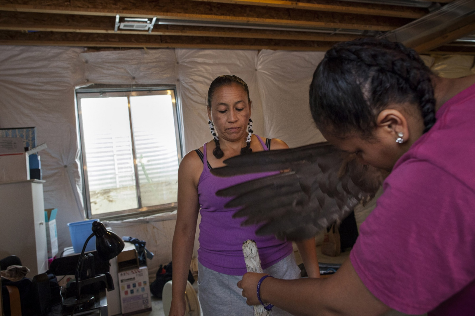 Aided by her daughter Tia, 17, Retired Sergeant First Class Mitchelene Big Man, 49, is cleansed with smoke from sage in a ritual before getting dressed for a performance in Pueblo, Colorado. 2014. SFC Big Man is originally from Crow Nation, Montana, and is a veteran of Iraq and the founder of Native American Women Warriors, an organization aimed at raising awareness about women veterans and Native American women veterans in particular. The Color Guard, which is the group of dancers representing the NAWW, often performs in powwows and events relating to veterans and Native Americans.