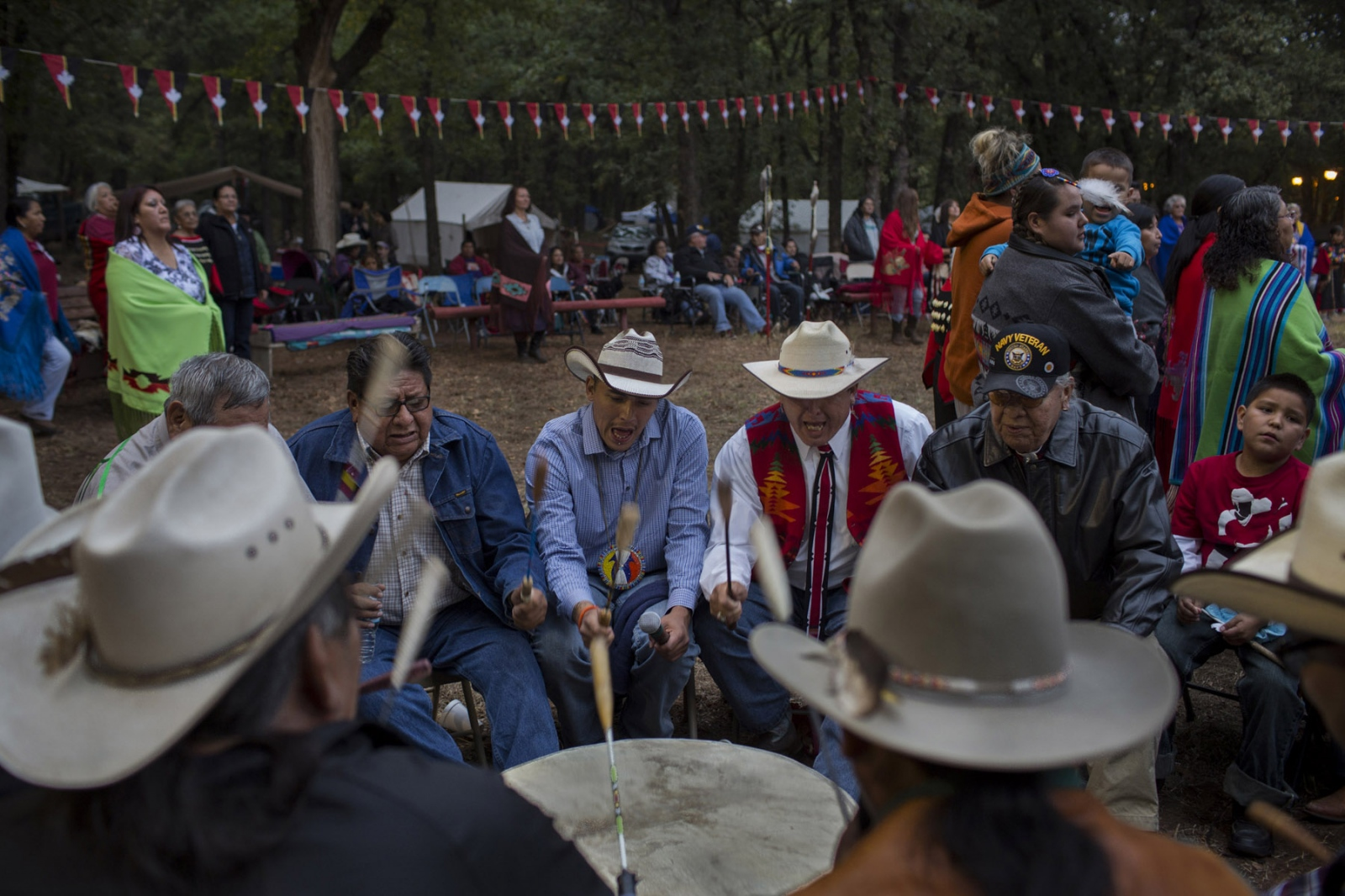 Singers drum to the beat of a tribal song during the ceremony remembering the veterans of the Kiowa tribe during their annual Black Leggings Society gathering near Anadarko, OK.