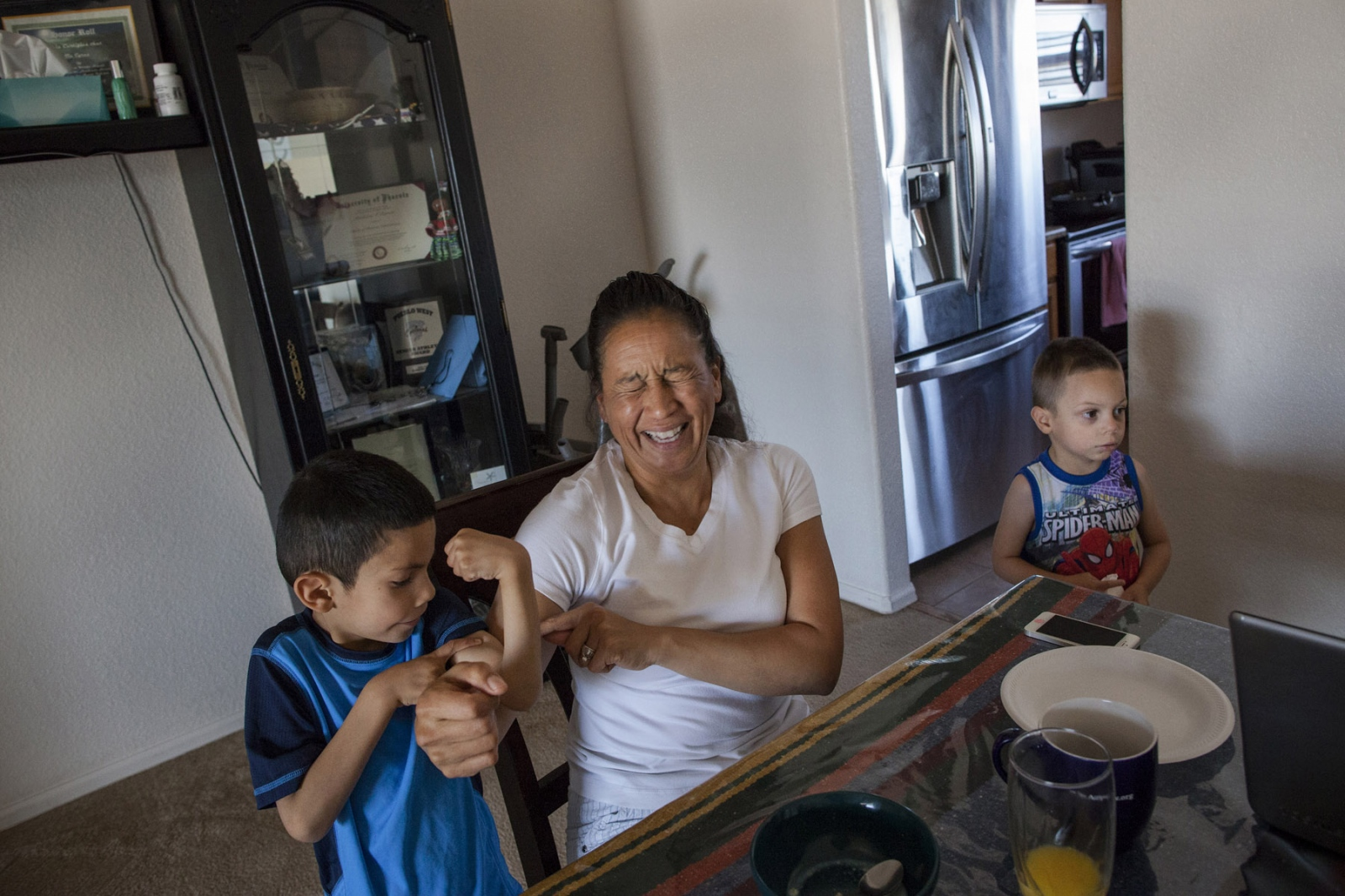 Retired Sergeant First Class Mitchelene Big Man, 49, plays with her adopted son David, 5, as Joey, 4, looks on at home in Pueblo, Colorado. 2014. SFC Big Man, originally from Crow Nation, Montana, is a veteran of Iraq and the founder of Native American Women Warriors, an organization aimed at raising awareness about women veterans and Native American women veterans in particular. She and her husband Dwayne Cyrus started the process of adoption of four children from Big Man's relative a year earlier.