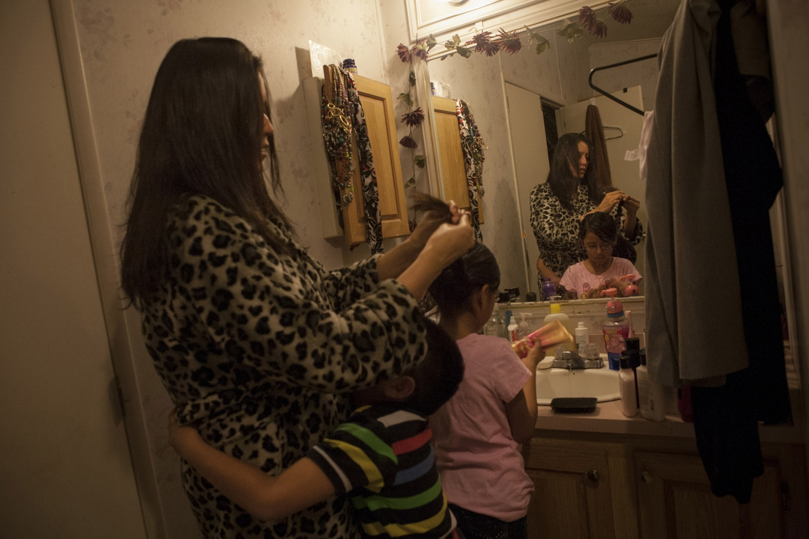 "Latonya ""Tasha"" Johnson, 35, wakes at 5.30am on weekdays to prepare herself and her children for the day, in Rock Springs, New Mexico. Pictured here is Ms. Johnson with her son Landon, 6, who was having a difficult morning and claimed he was sick, and her daughter Ashley, 8. Ms. Johnson says that the lack of time has prevented her from taking her younger children to counseling and that she knows they may not be able to verbally communicate how they feel about their father's death. Ms. Johnson's former husband Staff Sergeant Lonnie A. Watts, who died in October 2013, left Latonya to take care of their five children, the youngest of whom was born after he died. Mr. Watts was deployed to Afghanistan after the start of the US-led invasion with the 82nd Airborne, an airborne infantry division and was later deployed to Iraq in 2005. Ms. Johnson believes that her husband, whom she met after he returned from Afghanistan, was deeply affected by what he'd experienced in combat there, but refused to seek help or counseling to get diagnosed with PTSD because it was something ""[he] was not proud of."" Mr. Watts turned to alcoholism to deal with the trauma and according to Ms. Johnson, always needed an adrenaline rush. Ms. Johnson says she wishes her husband could have sought counseling so that he would be alive today to help her raise their five children."