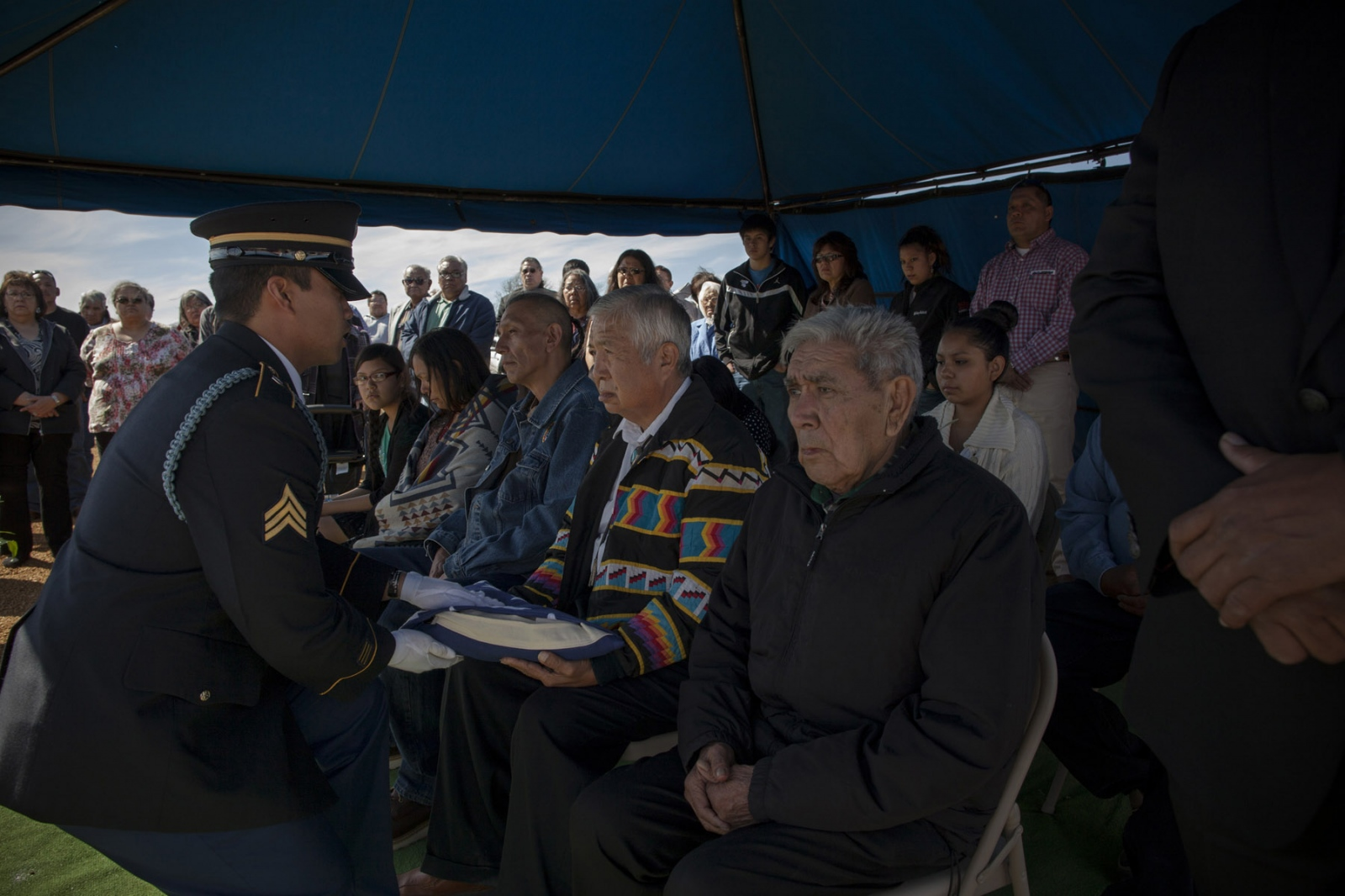 A soldier presents the folded American flag of a deceased veteran to next of kin, Rick Harjo, during funeral services for his uncle, Edmond A. Harjo in Seminole, Oklahoma, on Friday, April 4, 2014. Mr. Harjo was a Seminole Code Talker who served in Europe during World War II as a Private First Class and returned to the US after active duty in 1944 and remained in Maud, a nearby town, until his death at 96 on Monday, March 31, 2014. He was awarded the Congressional Gold Medal in 2013 for his efforts in using his language during the war. He was buried in the new veterans memorial grounds on the Seminole Nation and was given a small military funeral.