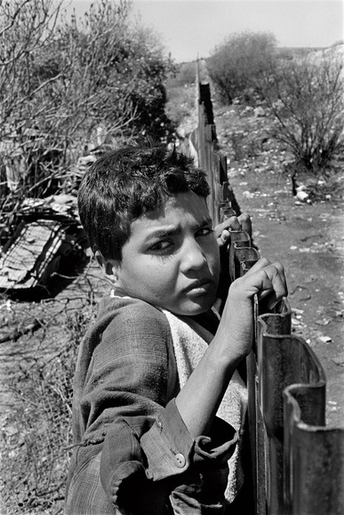 """Thirteen year old Geronimo stands at the fence of the US-Mexico border fence as he prepares to enter in the US. """"They cross over so they can eat better on the US side"""" Nogales, AZ. 05.95"""