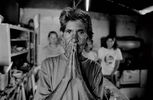 One woman prays for her families return home. Women are left behind to take care of the children as many of their fathers, husbands, and brothers (solos) cross the border to go to work in the US. Many of the families do not see the men in their family for years at a time. Nogales, Sonora, MX. 05.97