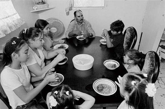 The Flores family eats dinner. Dinner is a family tradition and is often the only time the entire family gets together. Mecca, CA. 2002