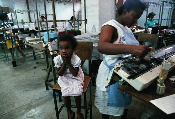 Day care Mauritius-style, finds a child close to her mother at a textile mill. The worker can earn a government-mandated monthly bonus for perfect attendance. Unemployment has virtually disappeared, thanks primarily to textile plants owned by local and Hong Kong investors. Tropical Mauritius is now one of the world's largest producers of wool sweaters.