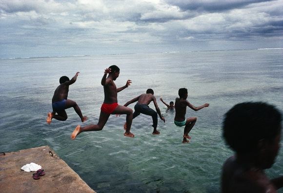 Jumping with the energy that has brought their nation an economic boom, young Mauritians leap into the warm waters of the Indian Ocean.