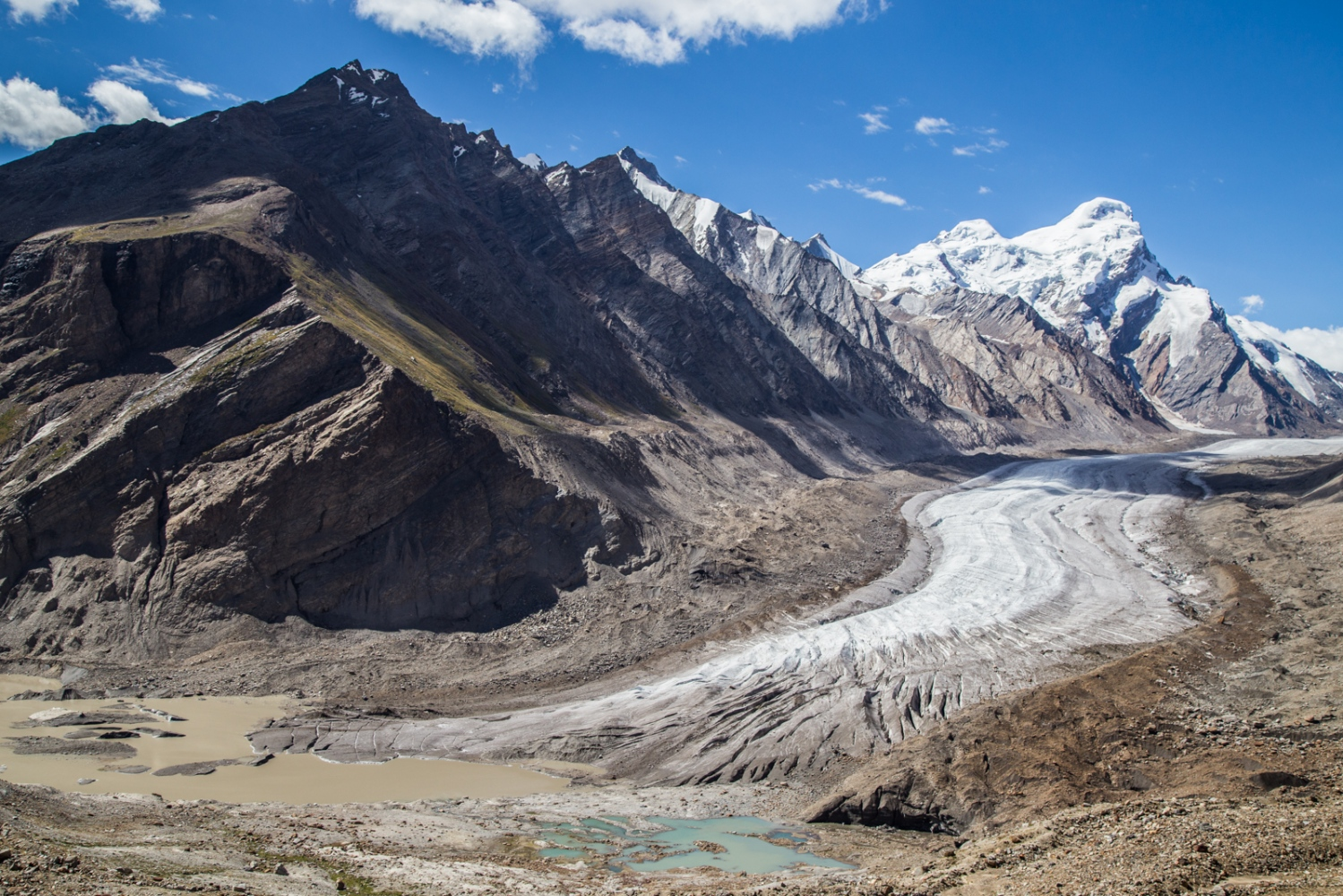 """The retreating Drang Drung glacier in India's Zanskar Valley. The global thermostat is being turned up by carbon and black carbon emissions and the glaciers are some of the first signs of a warming world. They are all melting at significant rates, especially so in the Himalayas. In this image pools of water are forming at the end of the ice that, according to locals, was hundreds of metres longer and thicker no more than 40 years ago. """"We used to go skiing on Drang Drung. Now it is impossible,"""" said Urgain Dorjey, a Zanskar local and trekking guide. Small streams are also forming on top of the ice."""