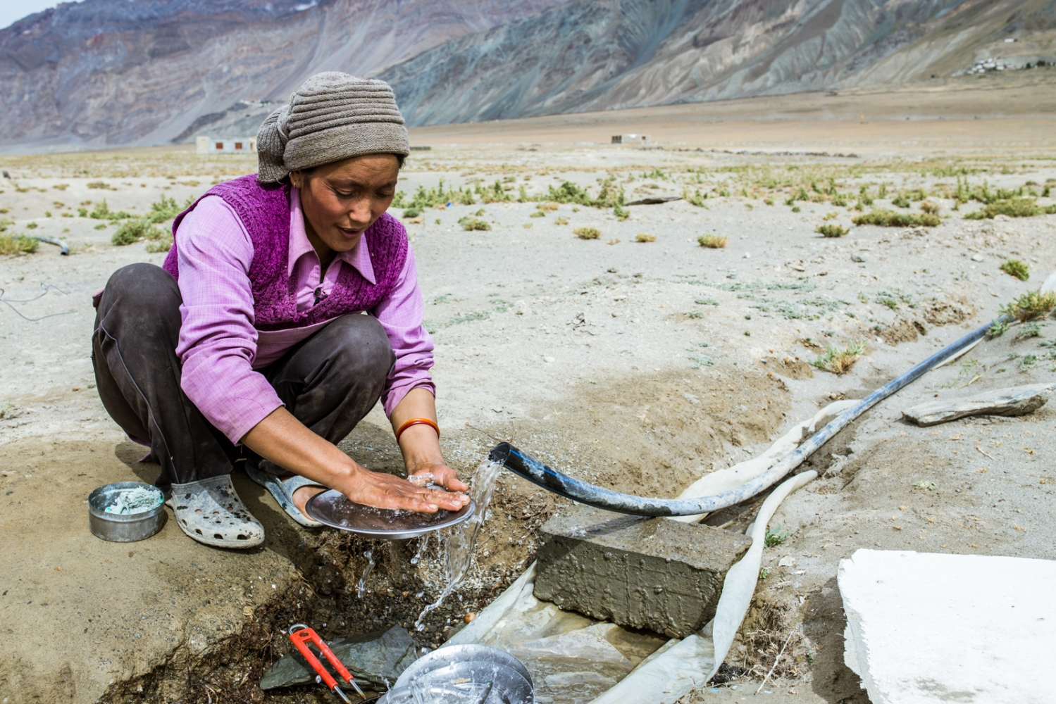 Thukjay Dolma, a resident of Lower Kumik, washes dishes under a pipe that brings water down from Kumik. Thukjay, put all her family's meagresavings into moving and building a new home. Once again, without water and savings, they are unsure of what the future will bring them.