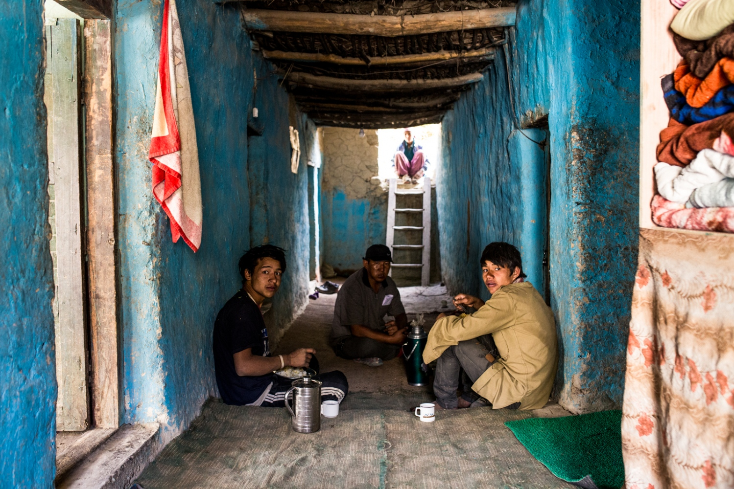 Tashi Stobdan, Tsewang Zangmo, and two Nepali migrant workers rest indoors on a hot day in Kumik.