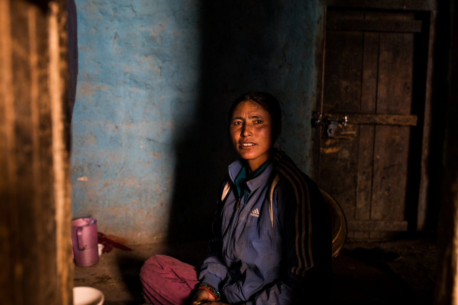 Tsewang Zangmo ponders in her home after a day's work in the fields.