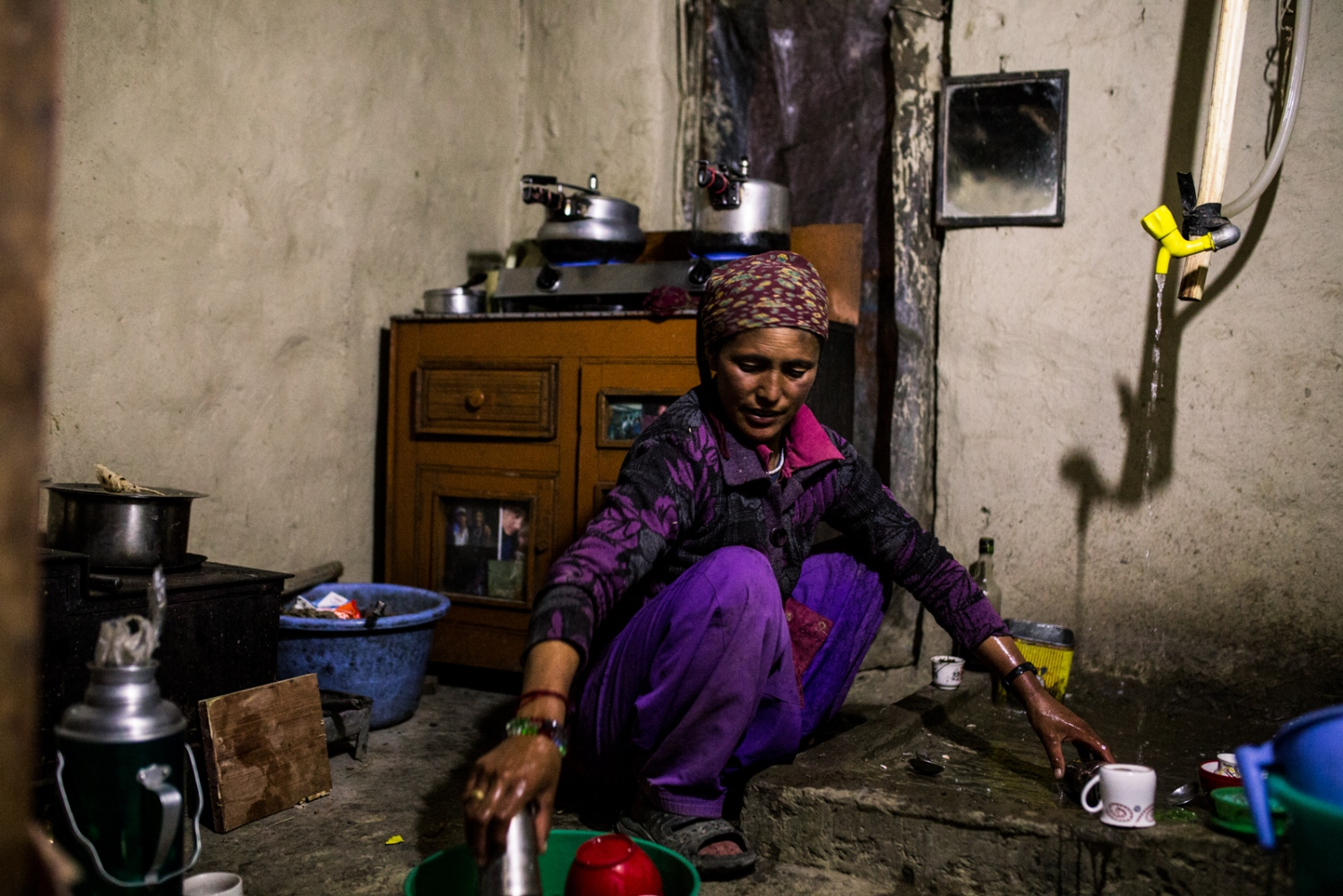 Tsewang Zangmo washes and cooks in her home kitchen with water coming up in the tiniest of trickles.