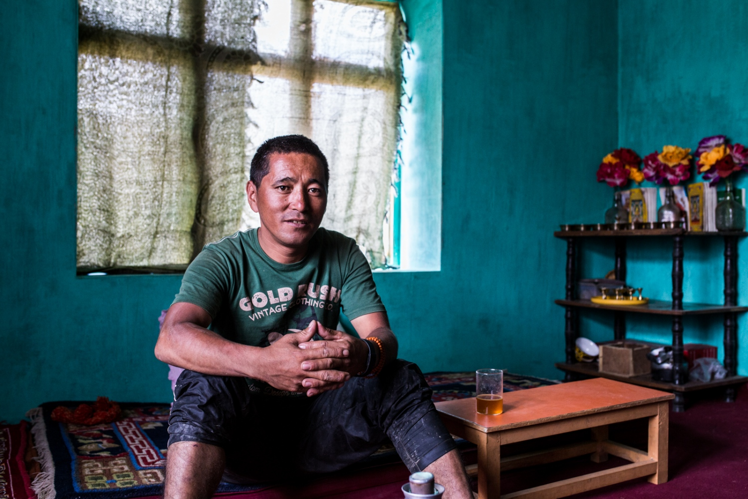 Bonchowk Chezen sits inside his new home in Lower Kumik. He is one of the lucky members of the new community. He has steady work in the Indian military and is able to provide for his family.