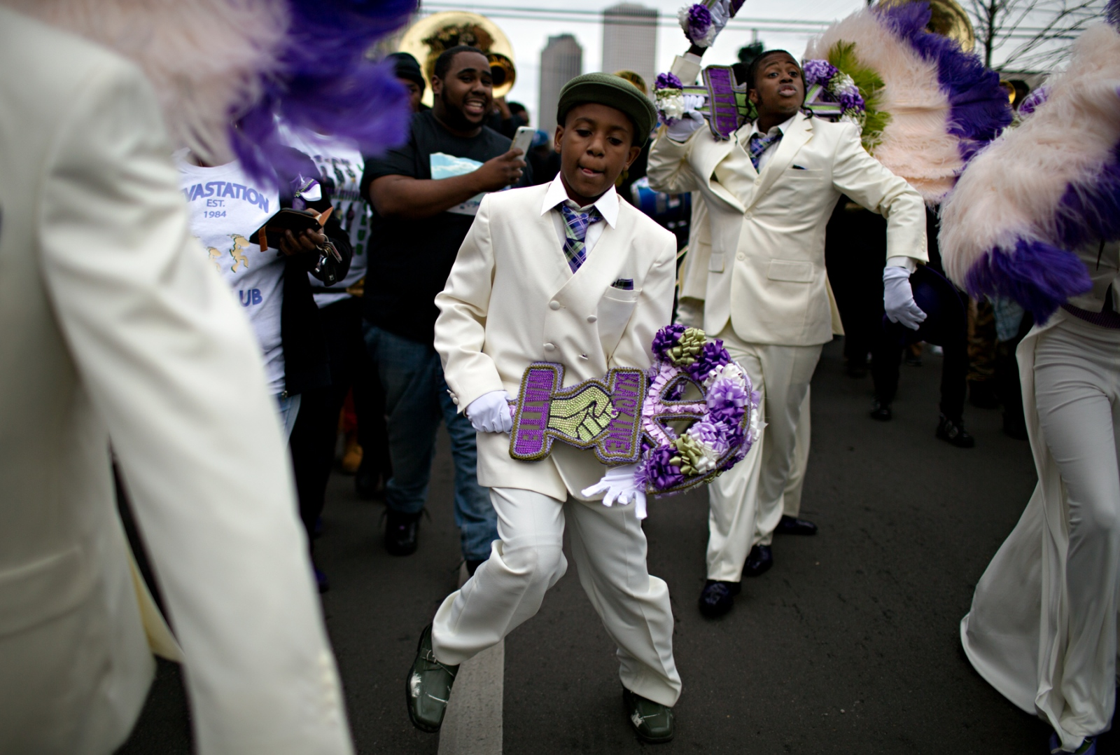 Holding a fan showing the Black Lives Matter logo, a young member of the Devastation Social Aid and Pleasure Club dances along during the Second Line Parade.