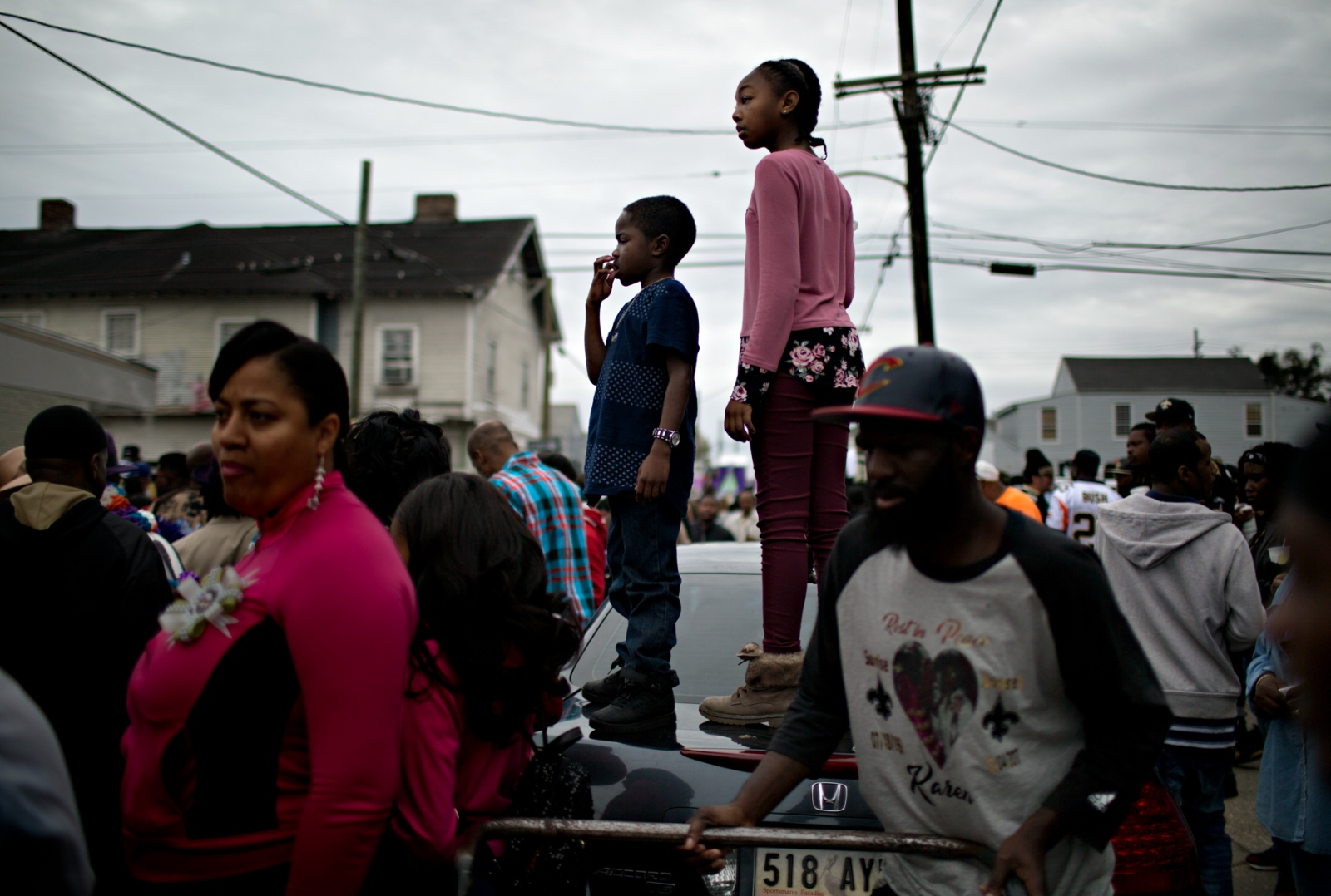 Two young participants and spectators watch the Second Line parade standing on top of a trunk of a car.