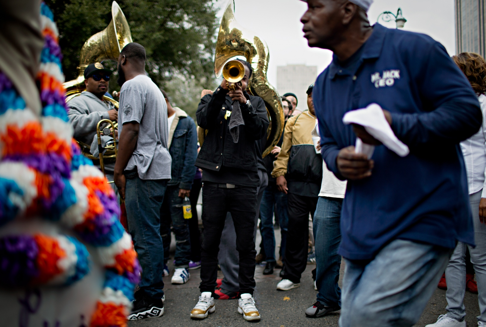 A musician plays his trumpet while other members of his brass band take a break.