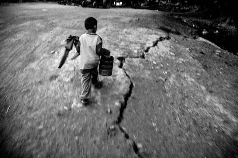 A large number of cracks were seen in the roads and villages of East Azarbaijan province after the 6.4-Richter earthquake. A 5-year-old boy is carrying oil to his family's tent.