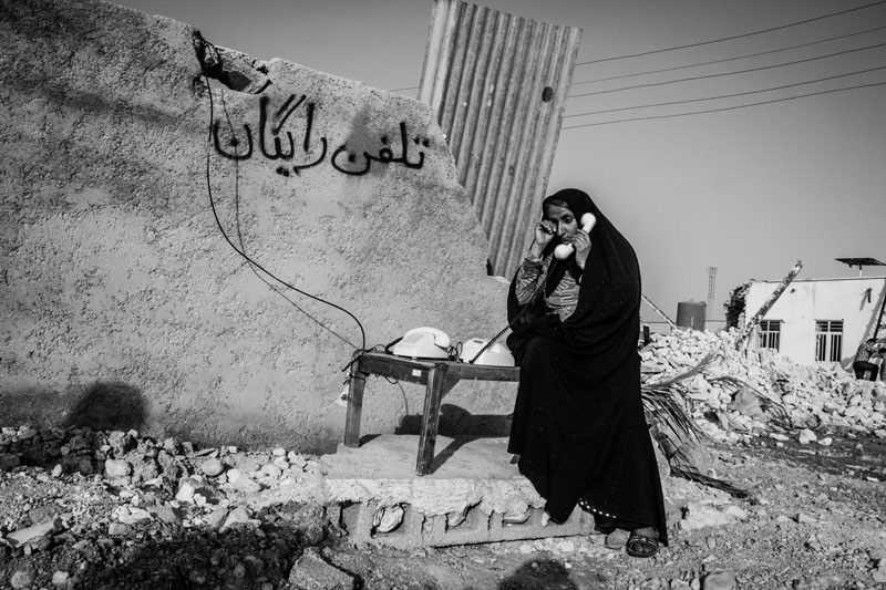 The 6.1-Richter earthquake in the town of Shanbeh in Bushehr province destroyed many communication infrastructures, including power and telecommunication lines. The officials allocated a number of free phones for people to contact their family members. A woman is in a phone conversation with her family members who are outside the town.