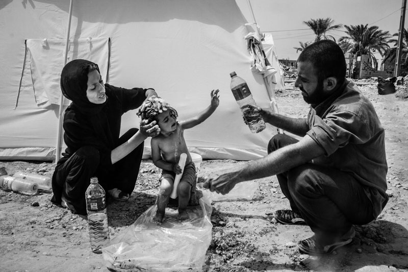 Given the destruction of infrastructures in the quake, people couldn't use baths for a long time. A mother and father are bathing their 3-year-old child with bottled water one week after the 6.1-Richter earthquake in Bushehr.