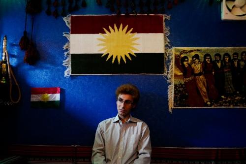 Japan, Tokyo, Warabi, 2017. Yilmaz posing for a portrait under the flag of Kurdistan inside Mesopotamia a typical kurdish restaurant in Tokyo.