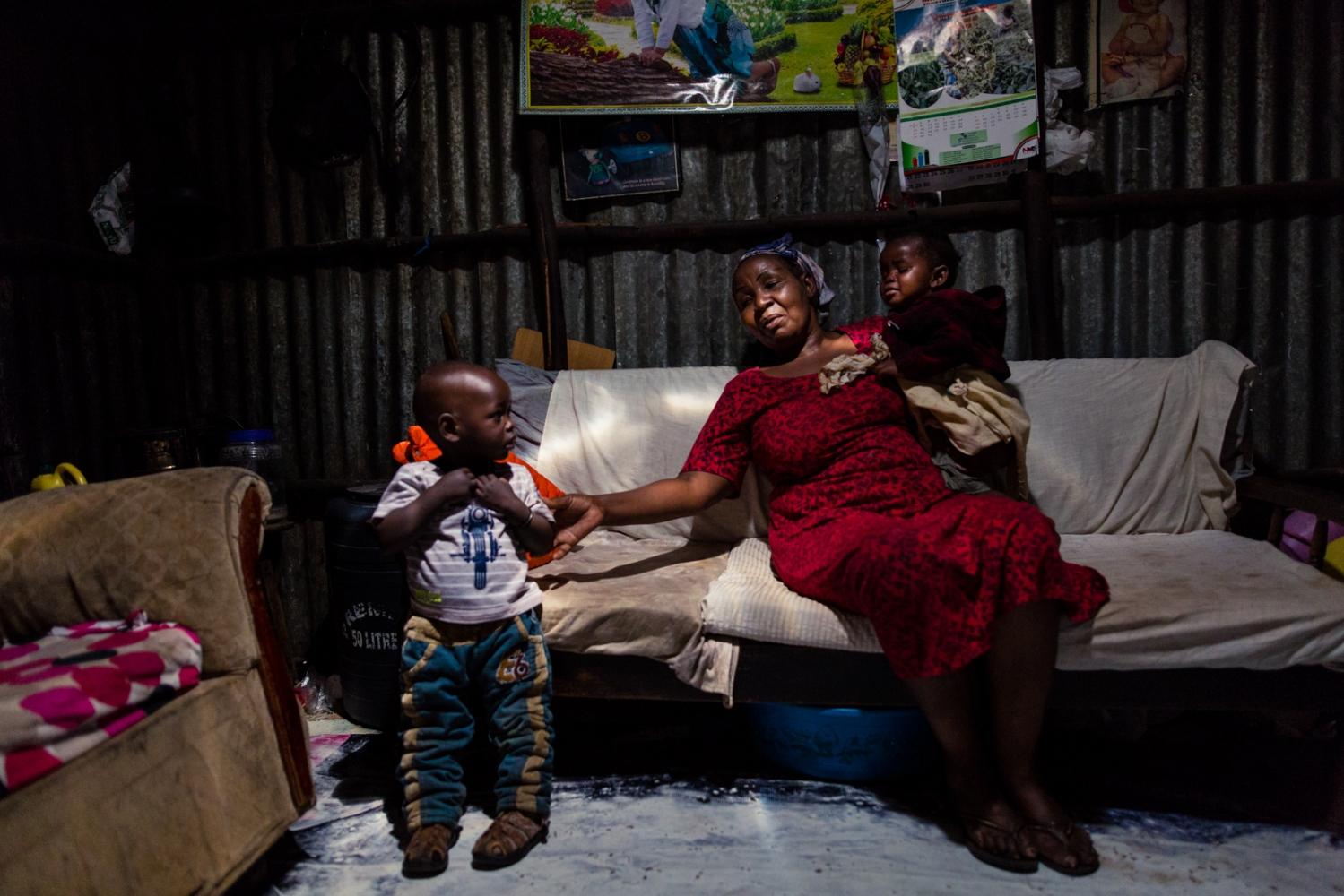 "Nairobi, KENYA, February 20, 2017: Elizabeth Kamau, 60, inside her hut in the Korogocho township with one of her ten grandchildren and the child of her adopted daughter. ""I like being a good role model to children by showing them that a woman can be strong and empowered"", she says. Elizabeth has been training with the 'Shosho Jikinge' (Engl.: 'Grandmother defend yourself') group since five years and has succesfully applied self-defense techniques to fight off potential sexual attackers."