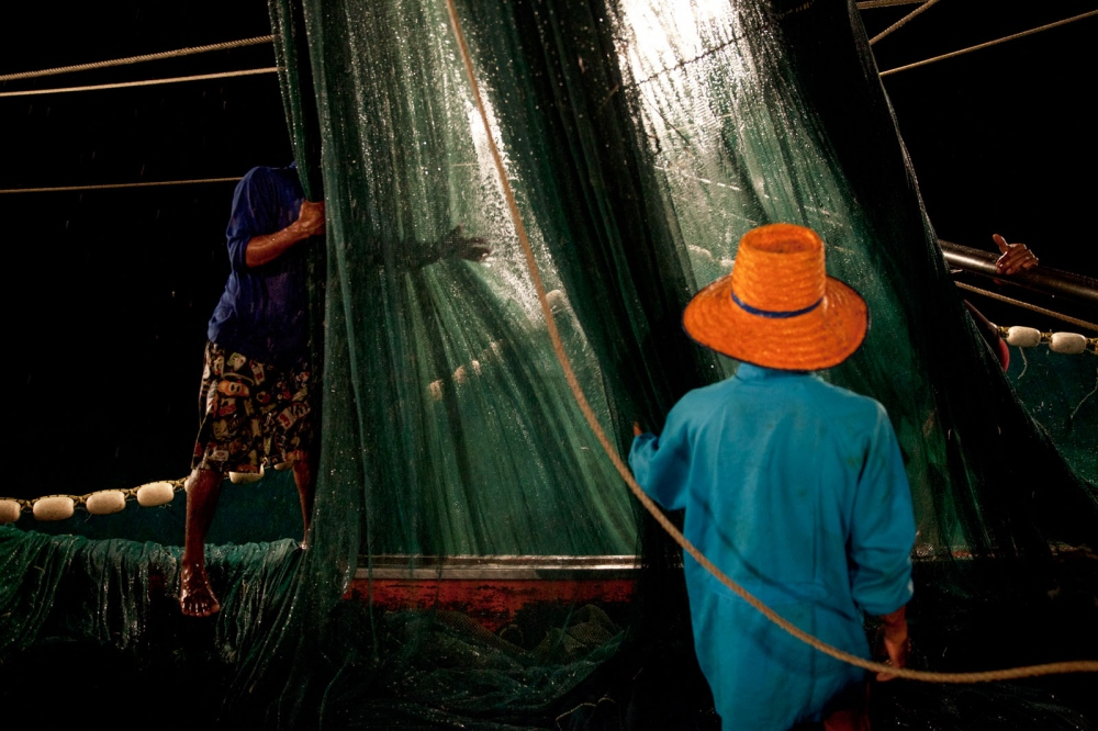 Burmese fishermen working all night on a Thai fishing trawler boat off the coast of Phuket pull in the net. Gulf of Thailand