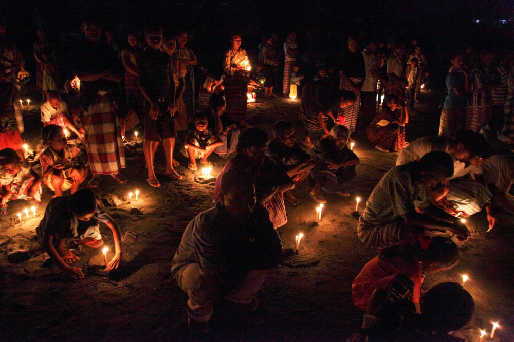 The fishing community of a remote Indonesian Island perform theceremony of 'Misa Arwah' on the beach. It is held once a year to commemorate those who died fishing and local fishing families light candles and place them all over the beach. It is small traditional fishing communities such as this that are effected by over-fishing due to large trawlers. Lembata Island, Indonesia