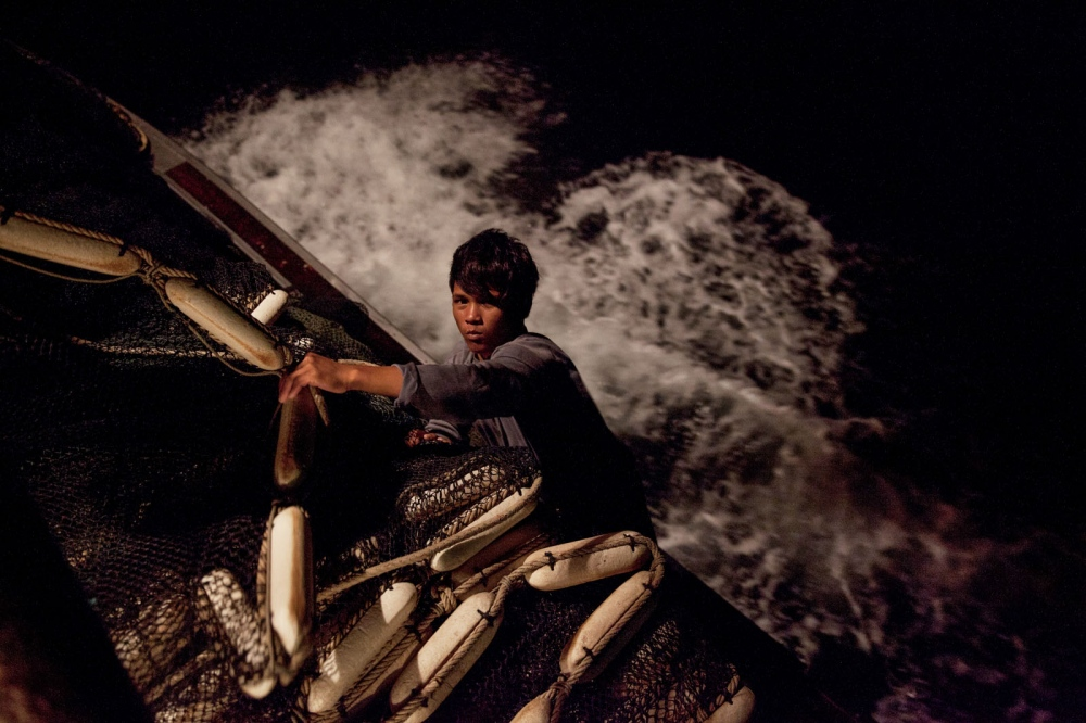 A Cambodian fishermen sorts the net, clinging on to the side of this Thai trawler boat as it ploughs through the darkness. Thailand is the third largest exporter of fish in the world after China and the US. Its fishing fleet is vast, but years of unregulated trawling has causes incredible damage to fish stocks. Chonburi, Thailand