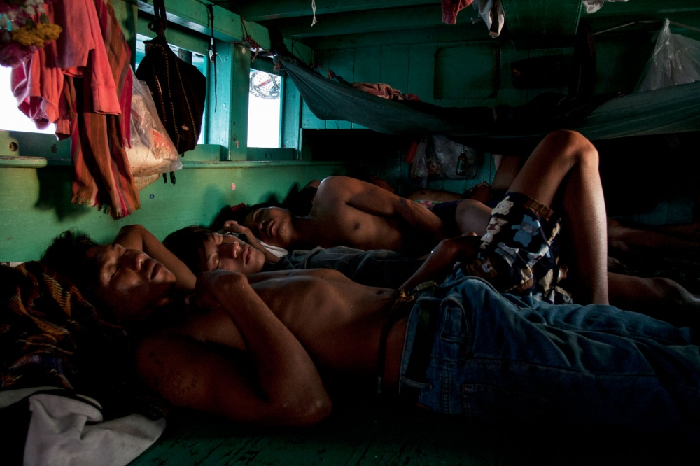 Cambodian fishermen sleep as the trawler boat returns to the shore at dawn after a night out at sea. Ang Sila, Thailand