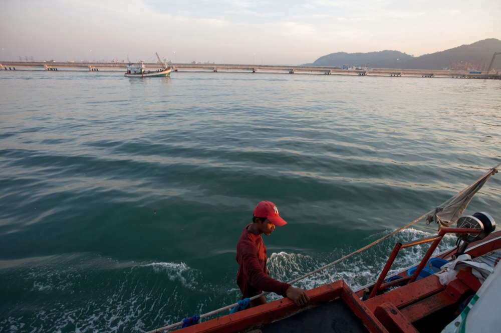 A Cambodian fisherman stands on the side of his boat as it returns to harbour after a night in the open ocean. Chonburi, Thailand