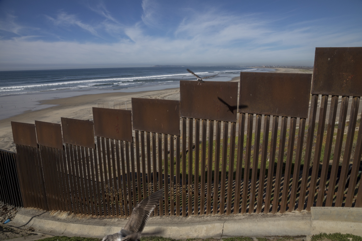 View of the U.S.-Mexico border from Playas de Tijuana, Mexico. The metal fence has been reinforced multiple times since the 1990s and it extends down to the beach stretching out some three hundred feet into the Pacific Ocean.