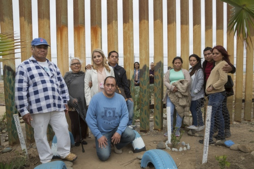 The Salgado family poses for a portrait. On the other side of the border fence (in the U.S.) Cesar Salgado and his niece Giselle visit with several family members (in Tijuana). On this day, Cesar Salgado saw his daughter for the first time in 14 years, only it was through the beams of the border wall.