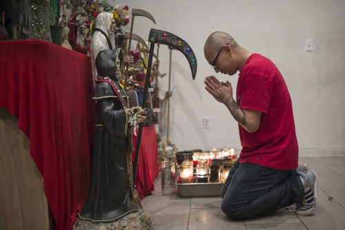 A devotee prays at a botanica store right before a monthly Rosary in Queens, New York. The altar at this botanica is also open to devotees who stop by and pray and bring offerings to the saint.