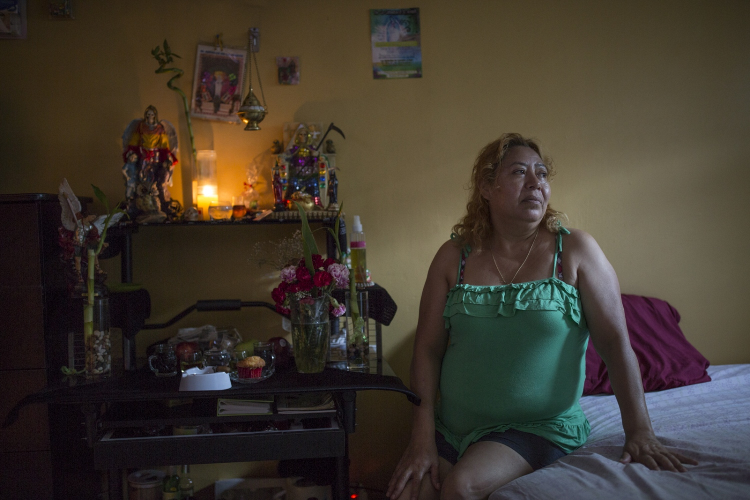 Santa Muerte devotee Conny Espinosa sits next to a Santa Muerte altar in her bedroom in Brooklyn, New York. Espinoza is an immigrant from Puebla, Mexico,