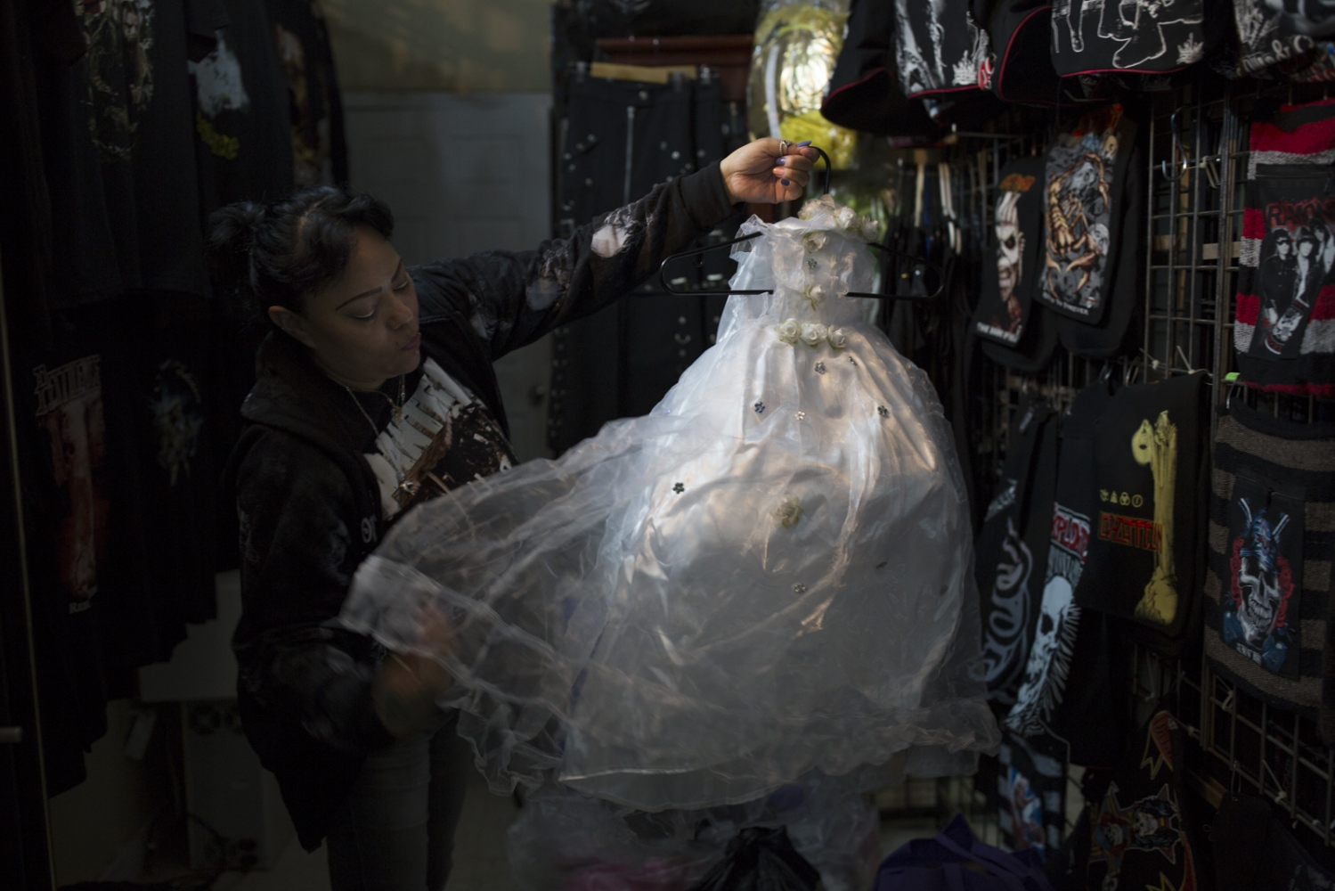 Guadalupe Mendoza unpacks Santa Muerte dresses to be sold at her store in Queens, New York.