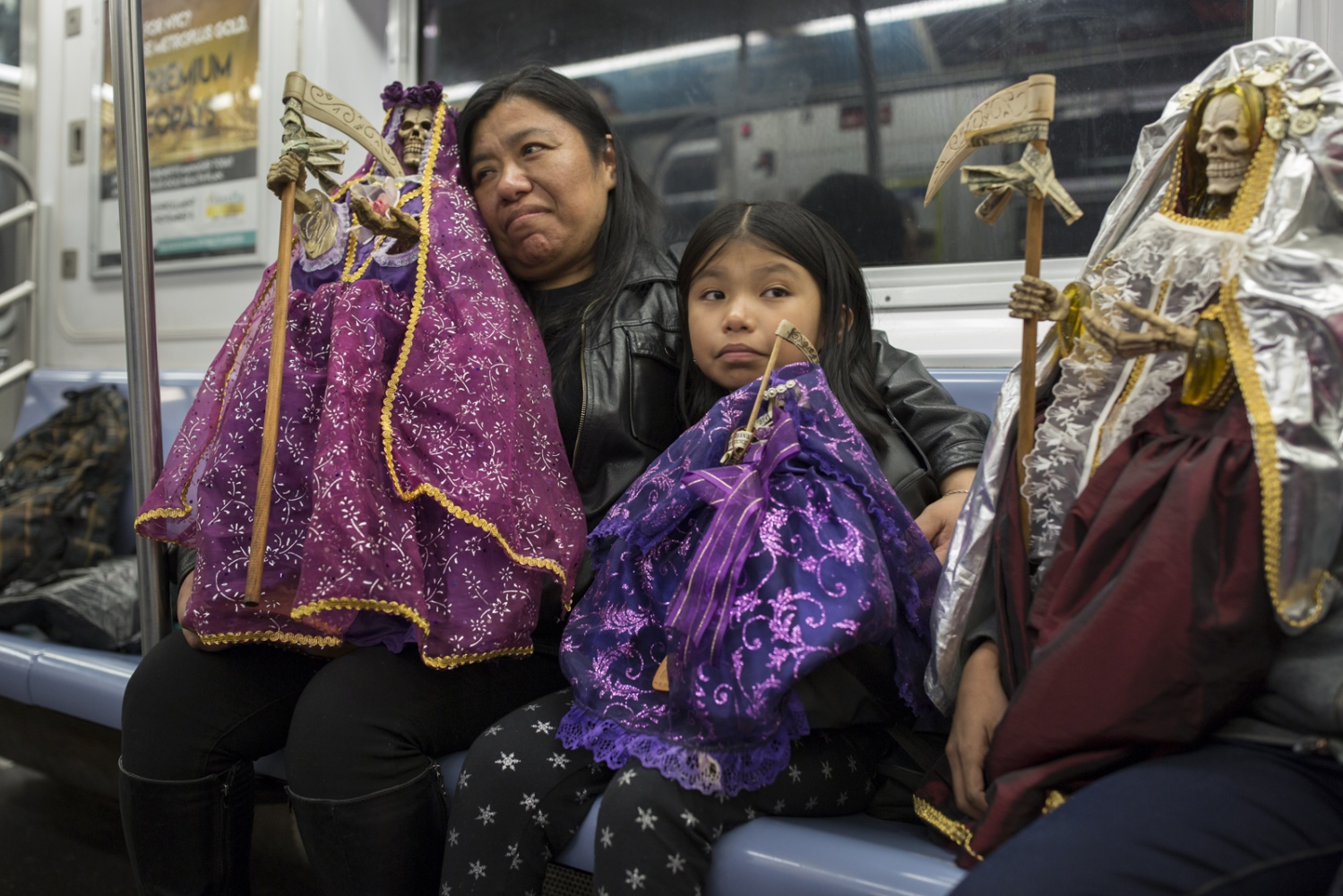 Santa Muerte (Saint of Death) devotee Rosa Perez with her daughter Karen and 2 other sons ride the New York subway with their Santa Muerte statuettes after attending a Santa Muerte event in Queens, New York. Perez became a devotee after an incident in which she almost died.
