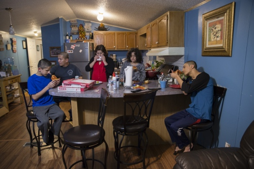 The Pineda family eats dinner together in their mobile home's kitchen area. The family moved to the area when Ricardo Pineda was discharged from the army in 2014.