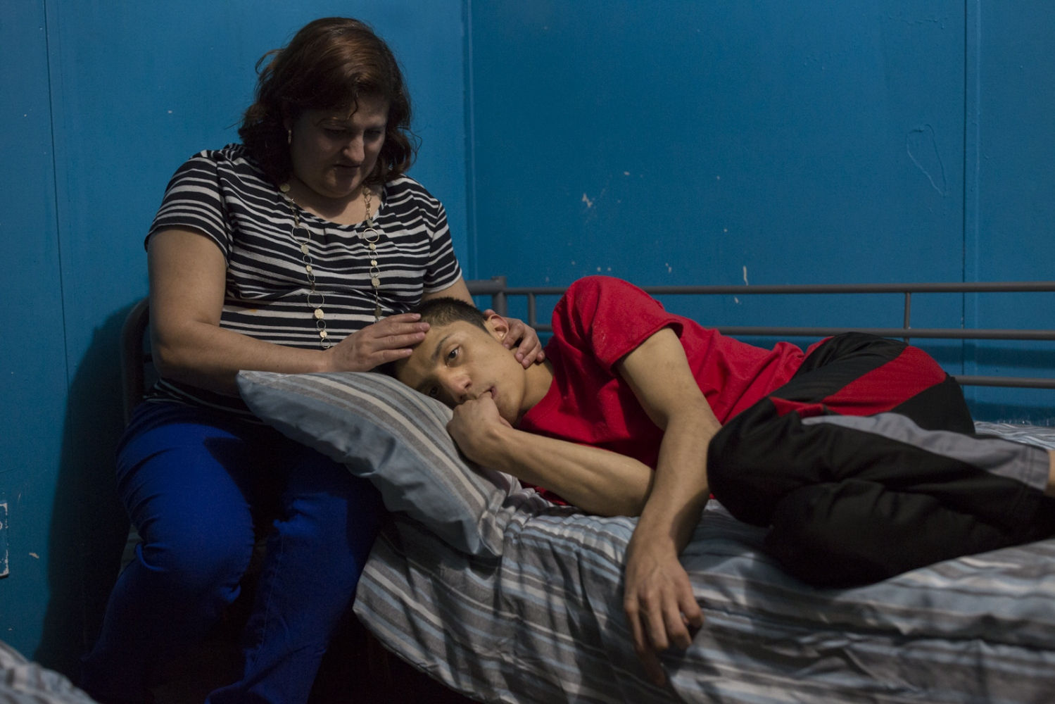 Veronica Castro caresses her son Juan Pablo in the bedroom that he shares with his 2 brothers. Juan Pablo has brain damage resulting from complications during a heart surgery when he was three years old and has been dependant on his mother ever since.